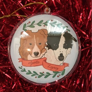 Holiday ornament with an illustrated portrait of two dogs named Apollo and Legacy