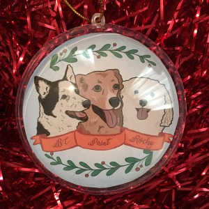Holiday ornament with an illustrated portrait of three dogs named BC, Paint, and Rocky