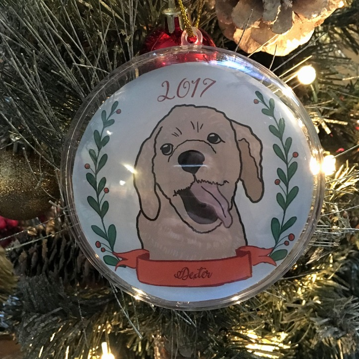 Holiday ornament with an illustrated portrait of a dog named Dexter