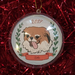 Holiday ornament with an illustrated portrait of a dog named Lola