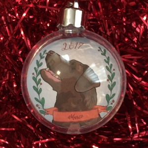 Holiday ornament with an illustrated portrait of a dog named Marco