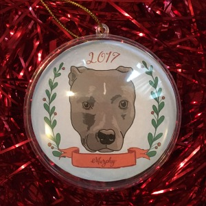 Holiday ornament with an illustrated portrait of a dog namedMurphy