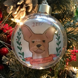 Holiday ornament with an illustrated portrait of a dog named Ronald Reagan
