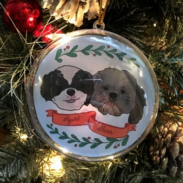 Holiday ornament with an illustrated portrait of two dogs named Squirt and Bean