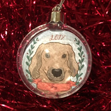 Holiday ornament with an illustrated portrait of a dog named Tony