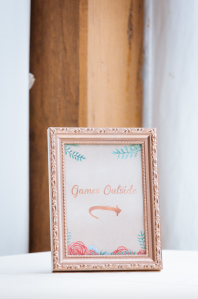 Framed sign that reads Games Outside with a calligraphic arrow that points outside.