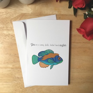 Greeting Card design with a sunfish that has long flowy brown hair. The text reads You are a cunning, pliable, chestnut-haired sunfish.