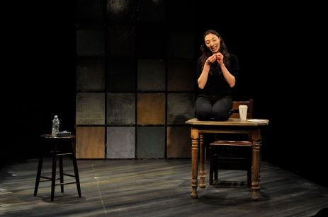 "Arielle Beth Klein sitting on a table gesturing with her hands in ""My Shiksa Boyfriend"". Photo by Lauren Bryant."
