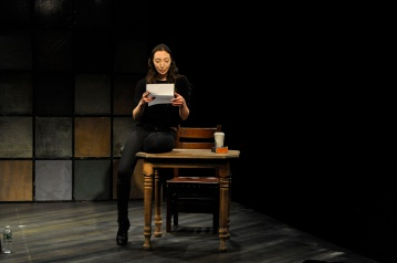 "Arielle Beth Klein sitting on a table reading a letter in ""My Shiksa Boyfriend."" Photo by Lauren Bryant."
