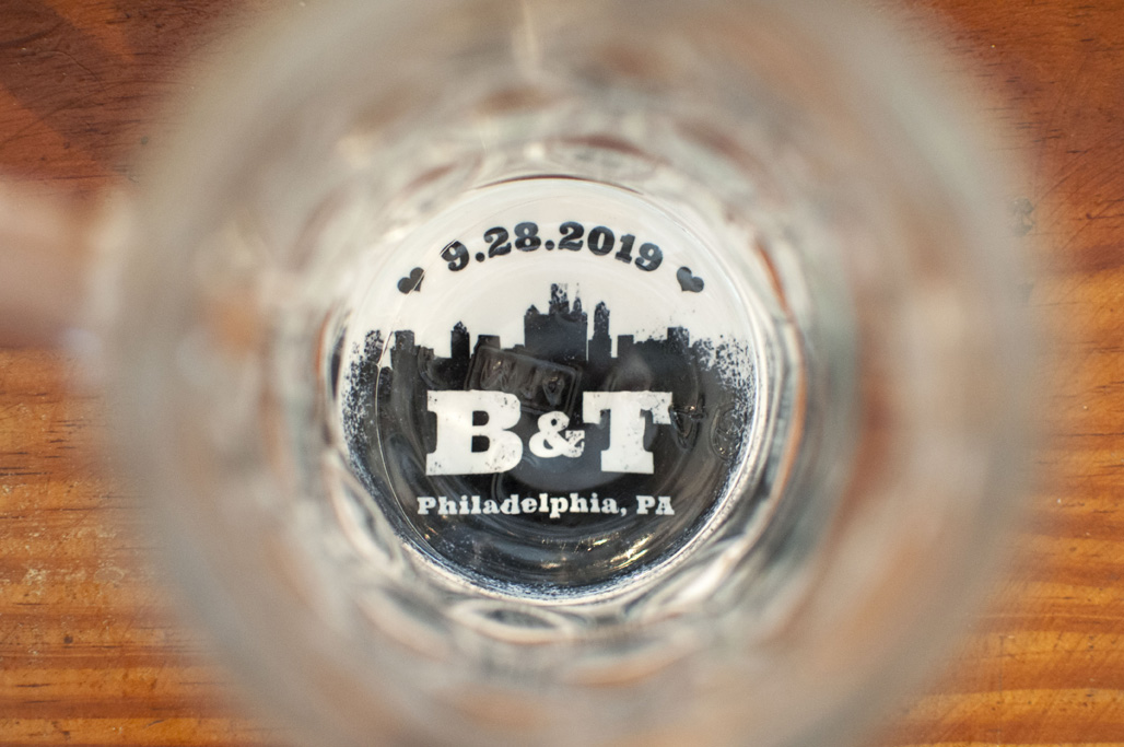 Looking through a beer mug, a coaster with a spray paint design that features the Philadelphia skyline and reads 9.28.2019 B&T Philadelphia, PA