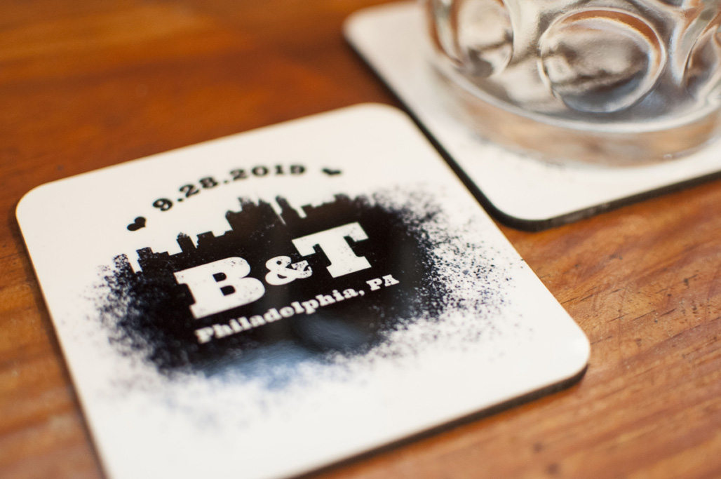 A beer mug next to a coaster with a spray paint design that features the Philadelphia skyline and reads 9.28.2019 B&T Philadelphia, PA