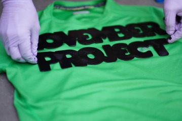 Image of a green t-shirt in the process of being tagged with the November Project logo