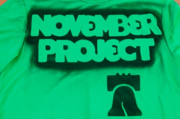 Image of a green t-shirt tagged with the November Project logo